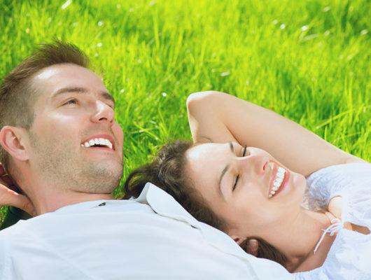 Zwei Personen lachend und liegend auf der Wiese bei herrlichem Wetter