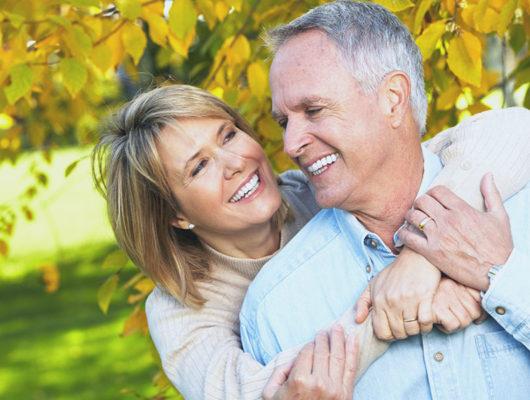 Lachendes Ehepaar im Garten mit gesunden Zähnen