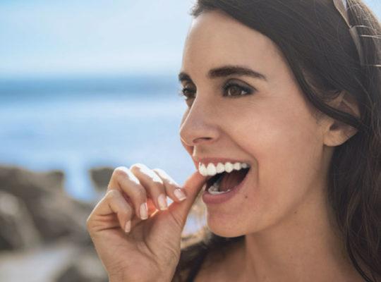 Frau mit durchsichtigen Invisalign® Zahnschienen