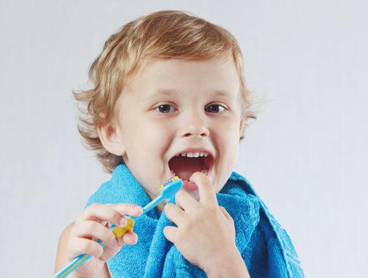 Kind beim Zähneputzen mit Handtuch