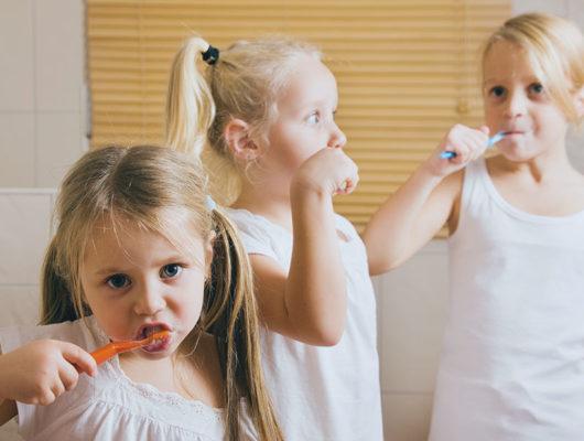 Drei weibliche Kinder beim Zähneputzen